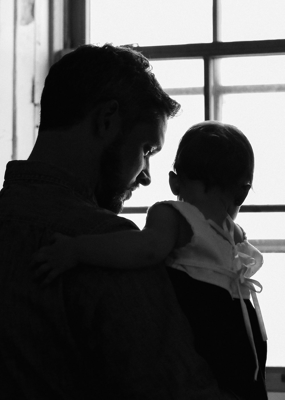 black and white image of a father holding his daughter looking out the window