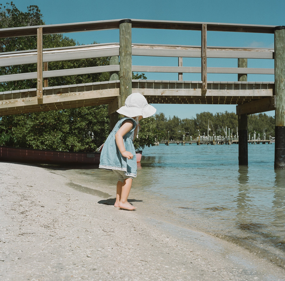 young girl walking towards edge of water in her summer hat