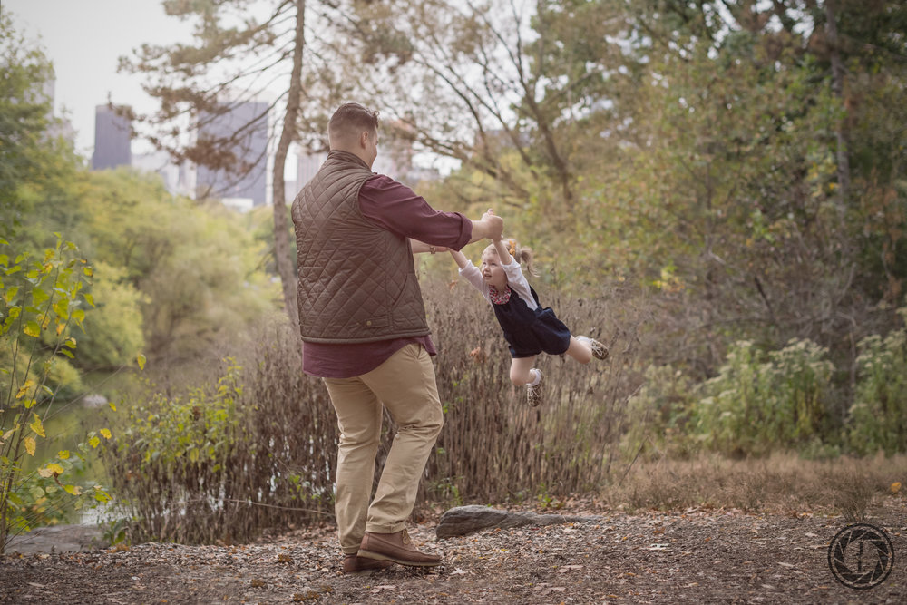color image of father swinging his daughter around in the park on a fall day