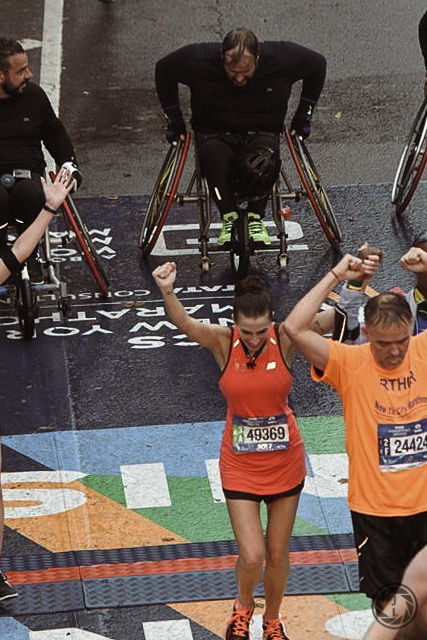 NYC Marathon Runners holding hands crossing the finish line