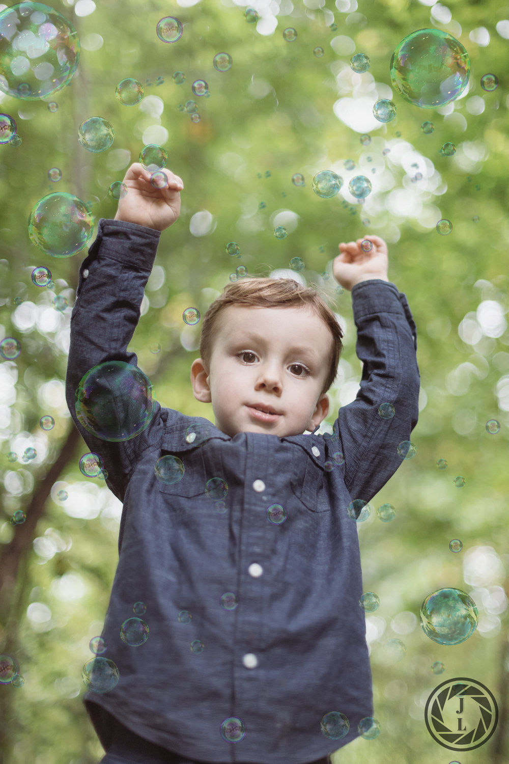 color image of a young boy waving his hands through bubbles