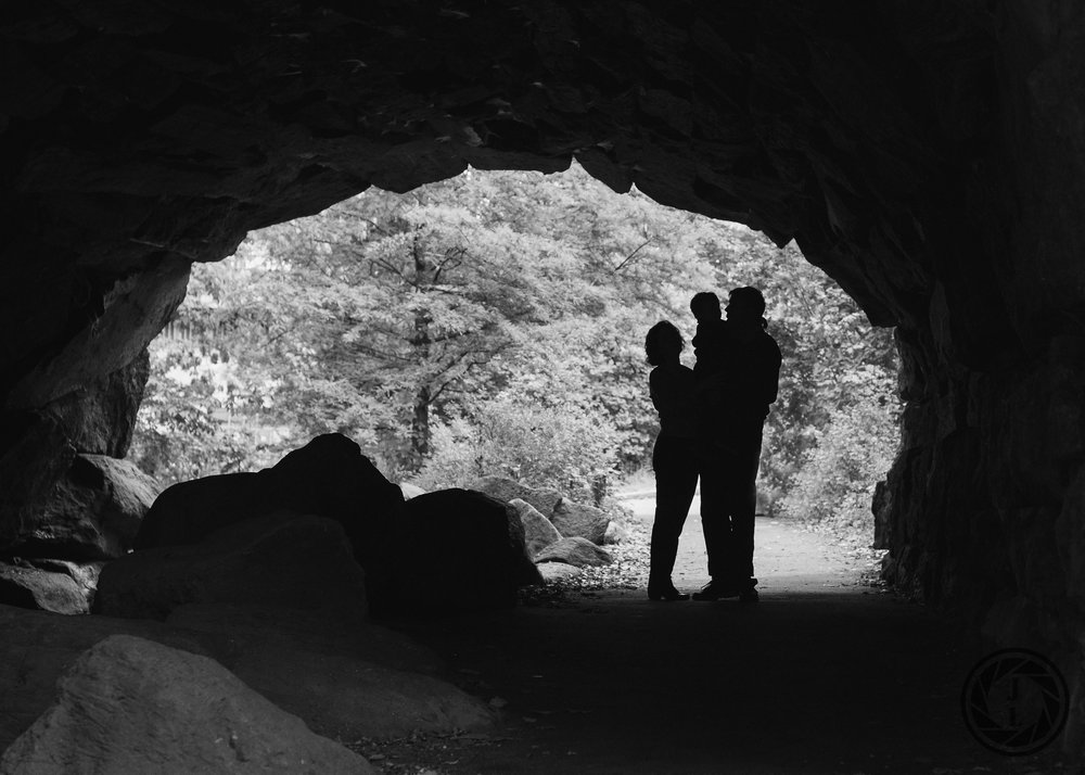 black and white image of a family under a stone tunnel holding their son in their arms