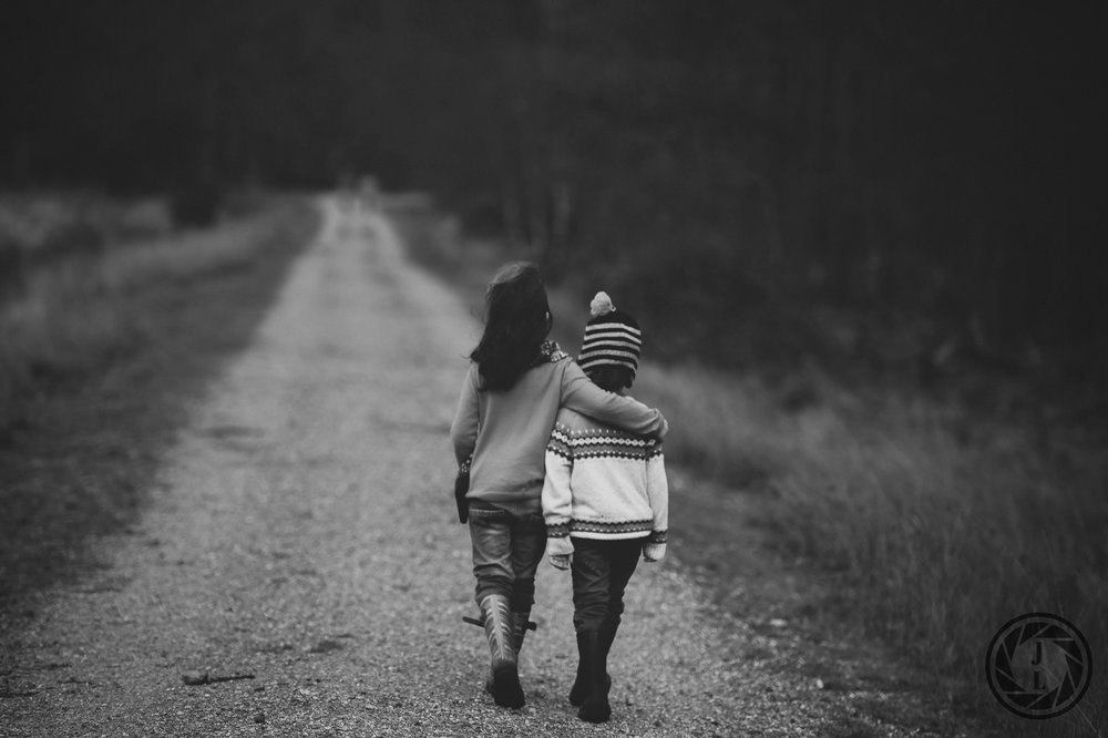 black and white image of two young kids walking arm and arm down a gravel road