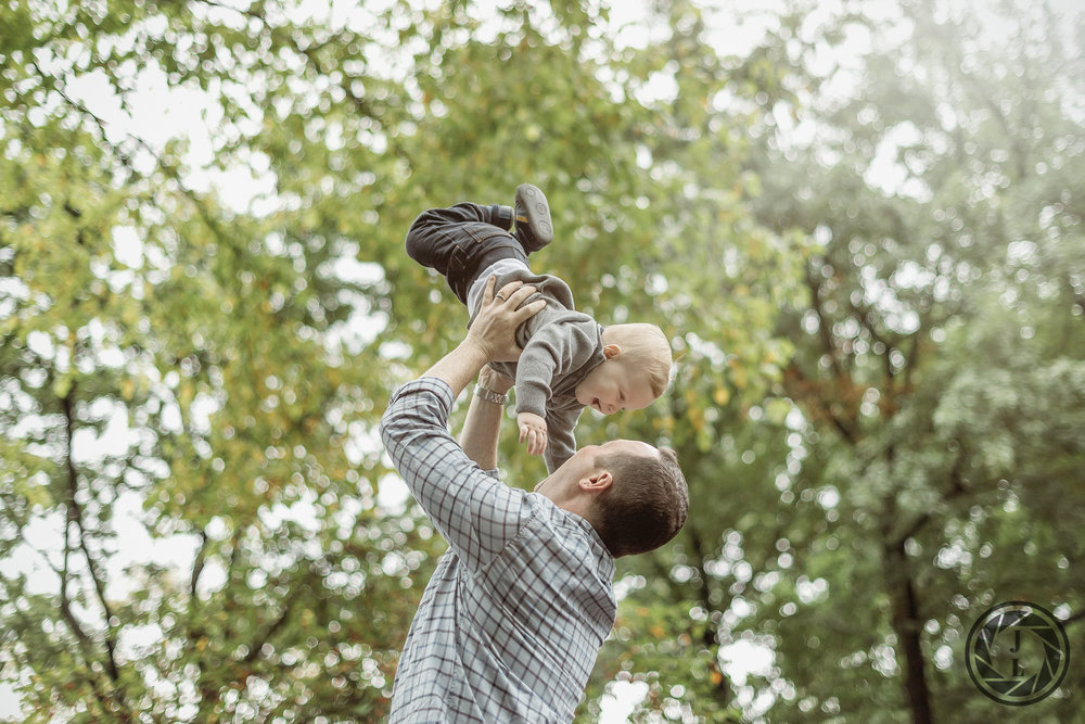 A father swinging his son through the air in Central Park.