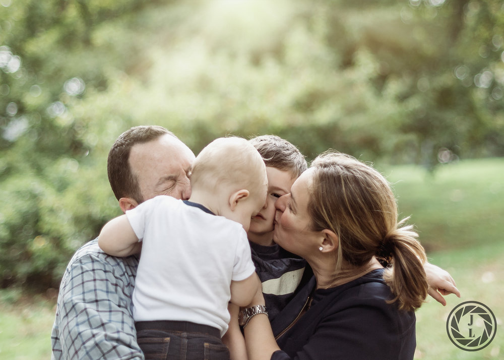 A moment of a family hugging, kissing, and laughing during playtime in Central Park