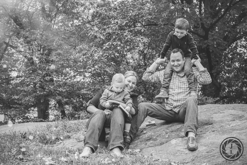 A family sitting together and smiling on top of a rock in Central Park