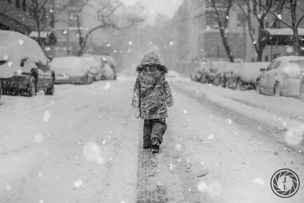 A littler girl walking down the middle of a New York City street during a snow storm.