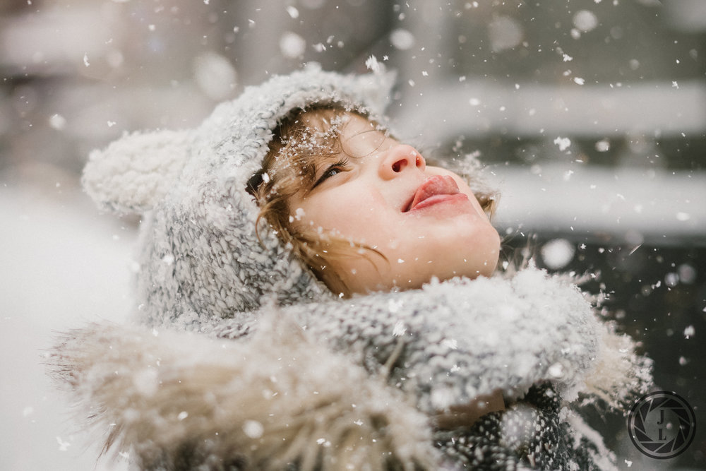 A littler girl eating snow flakes during a snow storm in New York City.