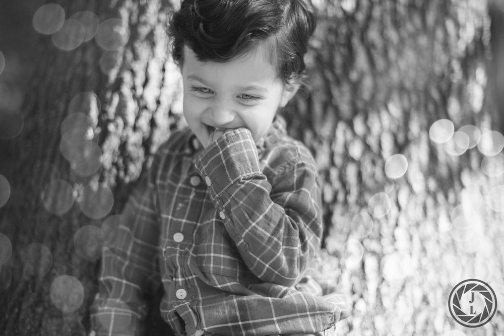 A black and white image of a toddler boy leaning against a tree.