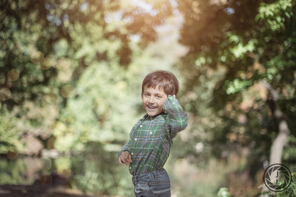 A laughing young boy smiling at the camera while playing in Central Park.