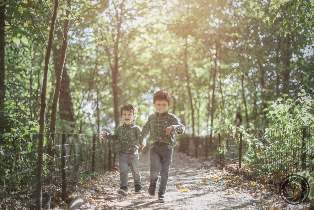 Two young brothers running on a trail in the North Wood of central Park.