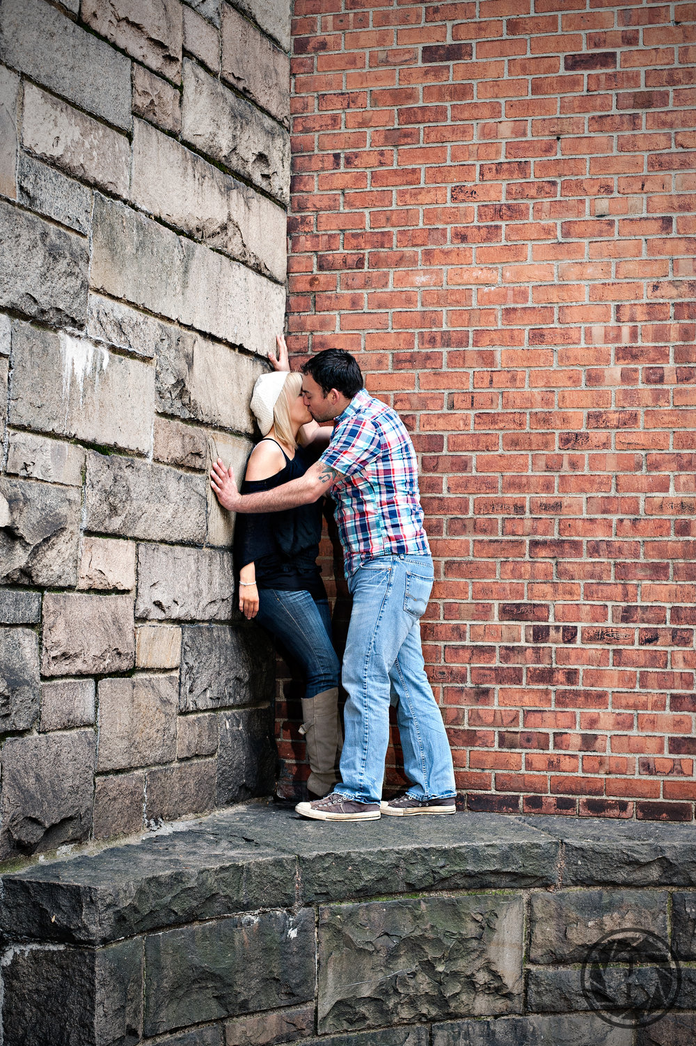 A couple kissing against a brick wall in Tudor City during their engagement photo session