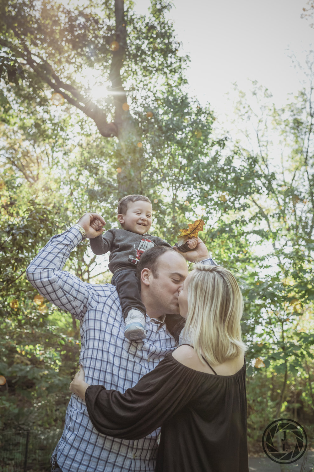 A mother and father kiss while their toddler laughs looking on from father's shoulder in Central Park