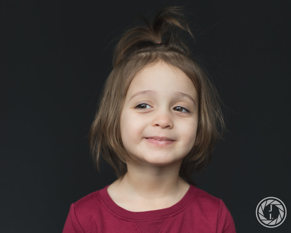 A toddler girl smiling while looking away from the camera.