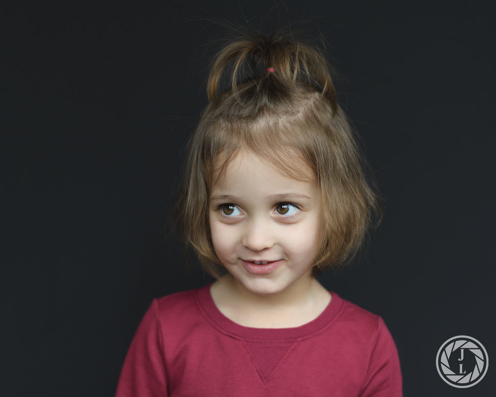 A littler girl in a ponytail looking away from the camera with a half smile on her face.