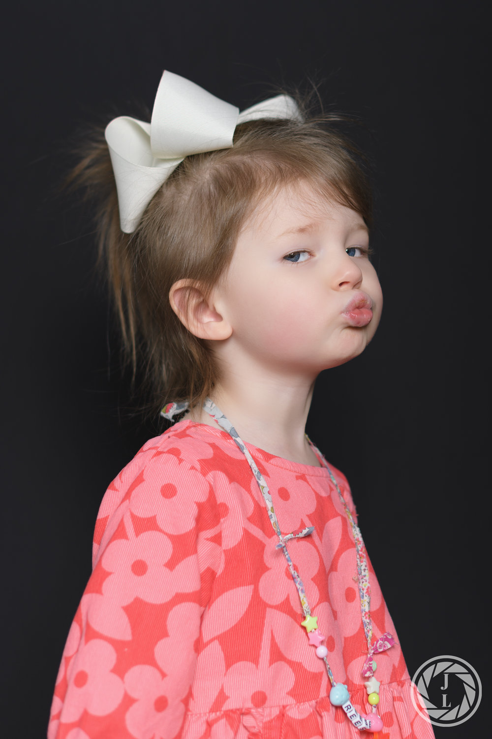 A toddler with a pink dress on starring sideways and blowing the camera a kiss.