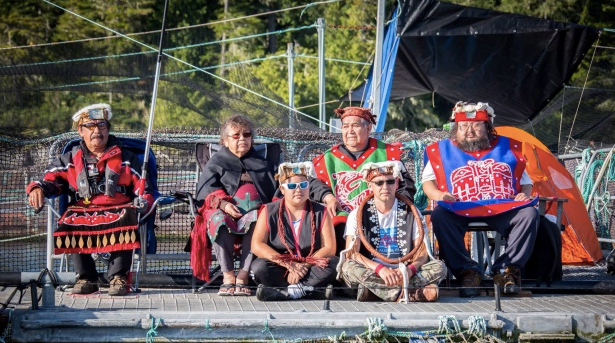 Protesters gather at the Marine Harvest fish farm on Swanson Island, near Alert Bay, B.C., in a handout photo from the Facebook page Swanson Occupation.  Ernest Alfred, 36, sitting cross-legged on the right wearing a cedar bark neck ring, sits with other traditional leaders from neighbouring villages. (The Canadian Press/HO-Facebook-Swanson Occupation)