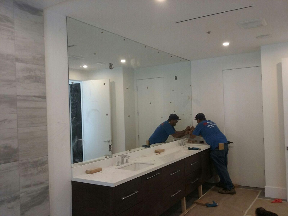 A custom vanity mirror with light fixture and outlet cutouts during the installation process.