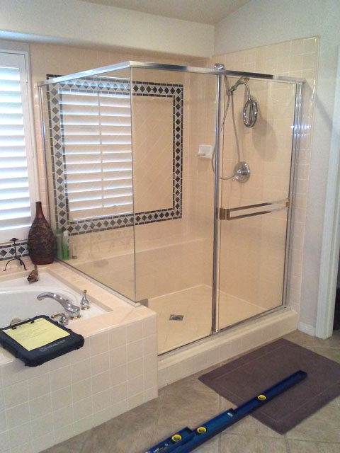 A framed swinging shower door with a towel bar in chrome finish.