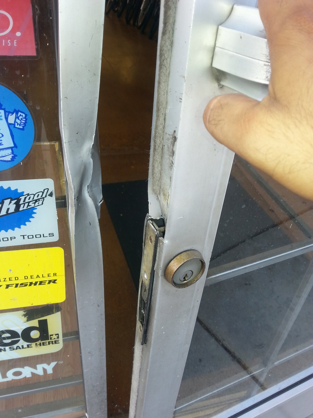 Example of a storefront door and frame damaged in a break-in robbery, Newhall CA