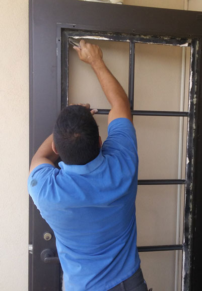 A National Glass technician installs a piece of replacement dual pane glass in a french door.