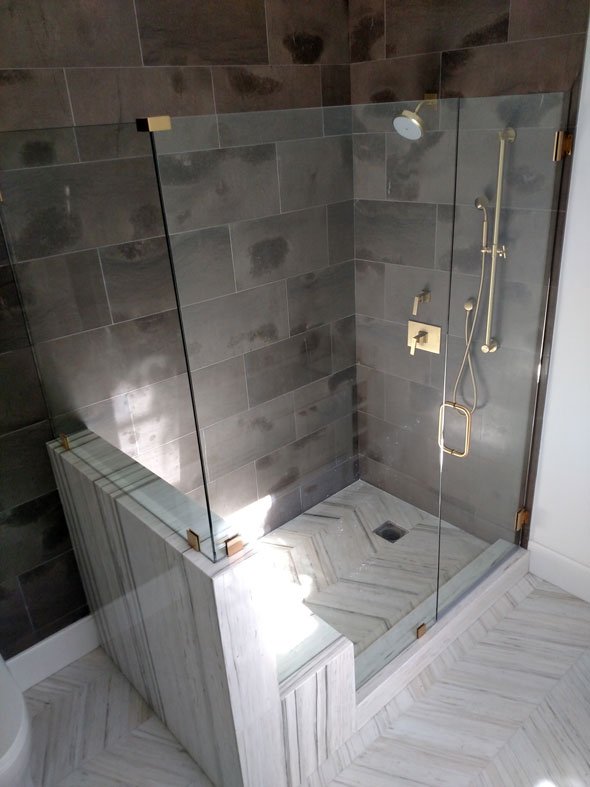 "A 3/8"" heavy glass shower enclosure with a double bench and brass hardware."