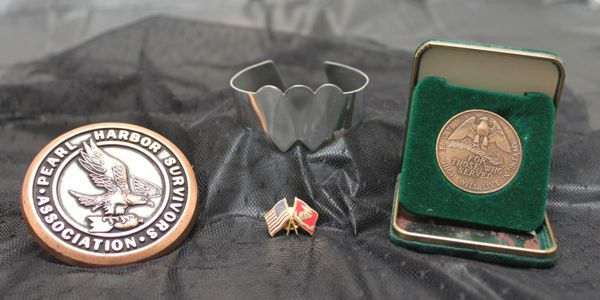 Sam Richiusa's medals, pin, and the Two Hearts Beating as One bracelet.