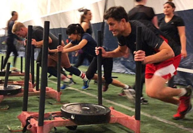 RUSH  This class will test your max-effort by challenging you with short, explosive intervals with quick rest periods. Expect your entire body to be tested with compound movements, sprints, agility ladders, sleds & more! Participants can expect to develop strength, cardio and power. Bring on the sweat!