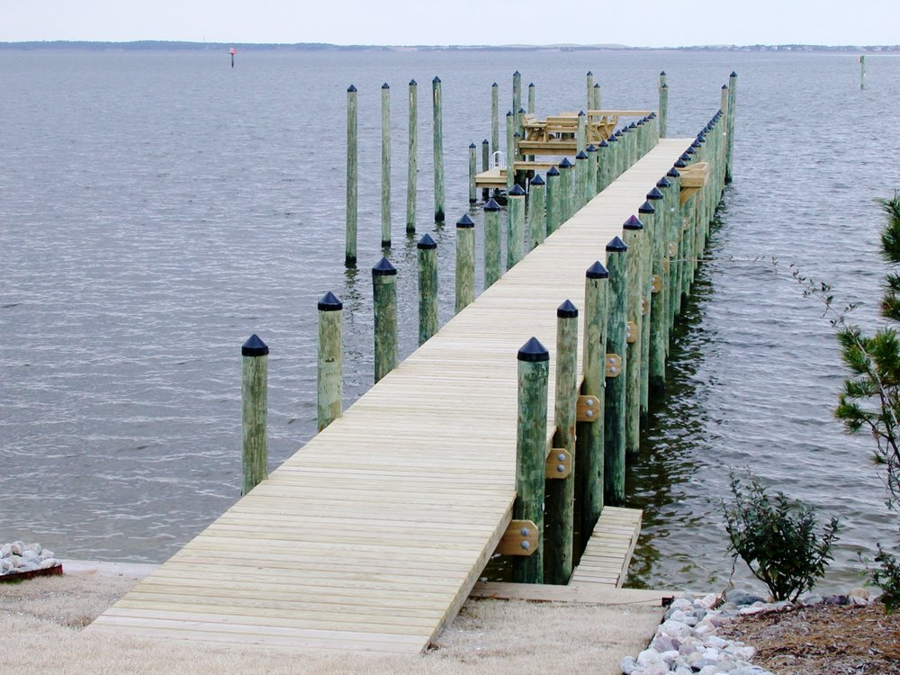 "Docks and Piers - New construction consists of 8"" round diameter 2.5 CCA treated pilings that are jetted in the ground with a minimum of 10' of embedment, treated framing bolted together with galvanized hardware, and #1 Grade Pro Decking secured with stainless steel screws."