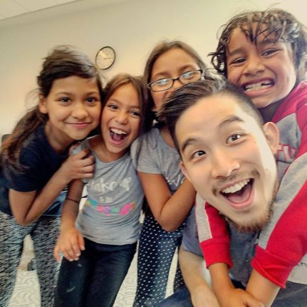 Justin Chan surrounded by children smiling