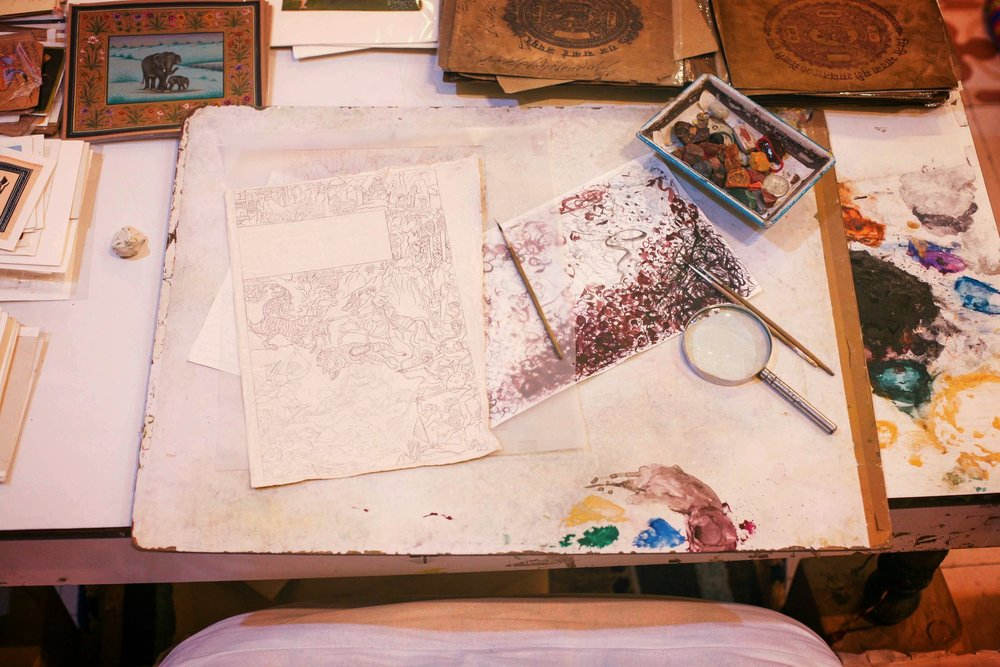 Miniature Painting work station in Jaipur City Palace, featuring mineral stone palette, single-hair paint brush, antique rice paper and magnifying glass.