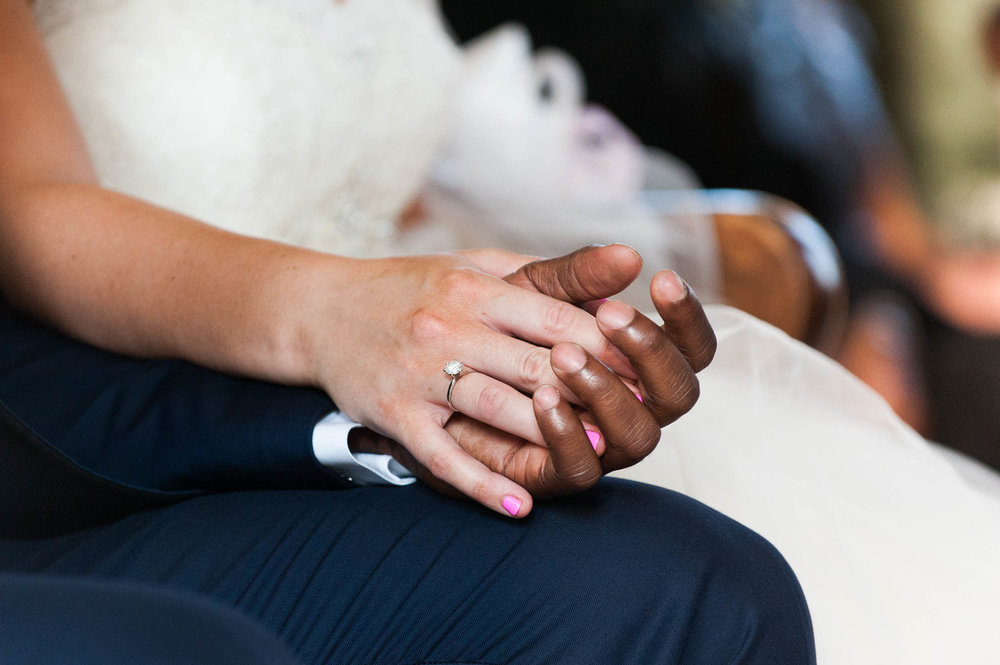 A bride and groom hold hands during their wedding ceremony.