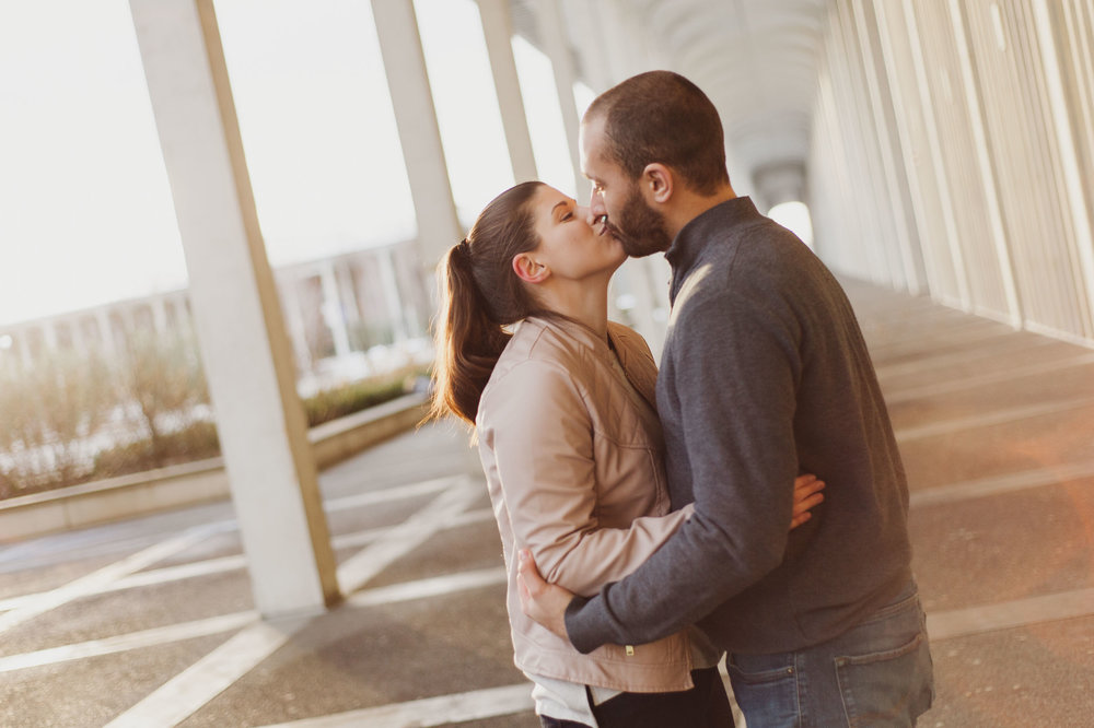 A young caucasian man and woman kiss as the rising sun shines on them at the University of Albany campus.