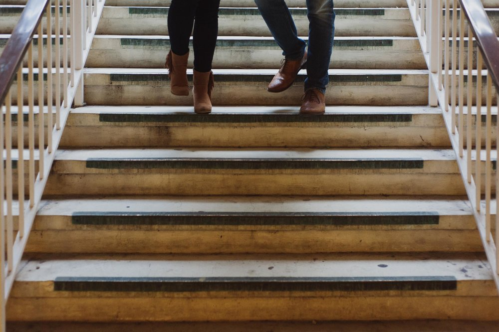 The feet of a man and woman walk down stairs at the University of Albany campus.