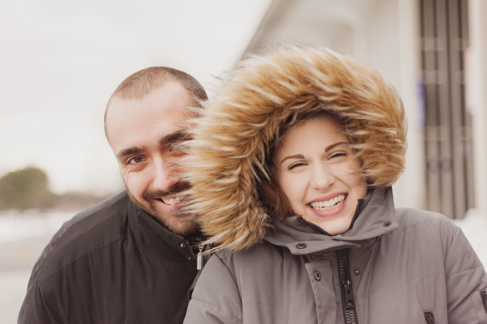 A young Caucasian woman wears a hood with a faux fur and smiles joyfully as a young man peaks out from behind her hood.