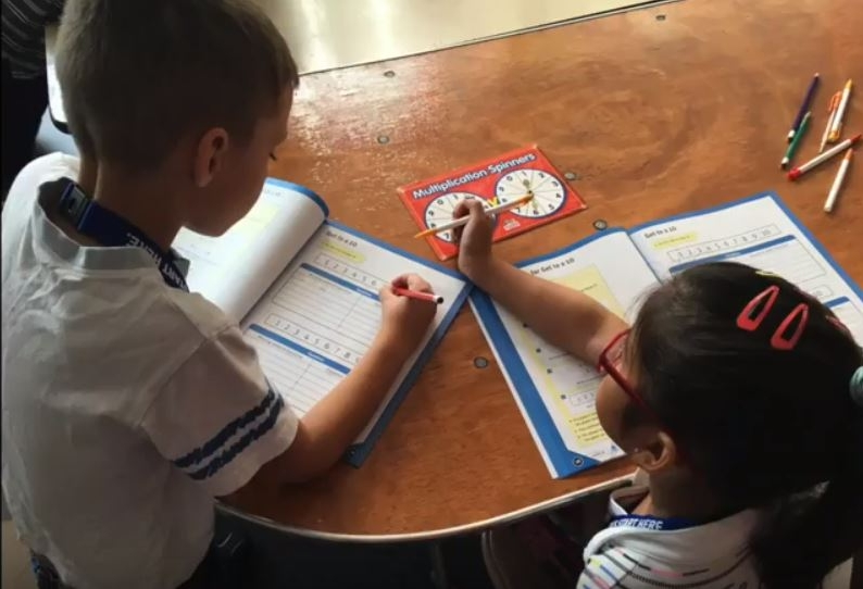 Summer Photo 2 boy and girl with workbooks.JPG