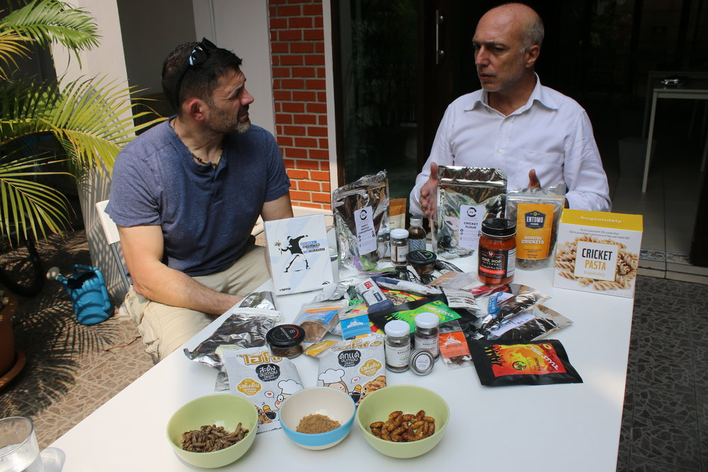 Bill & Massimo talking about the nutriental benefits of eating insects while the table is covered in edible insect food products from around the world.
