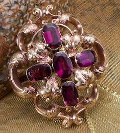 Amethyst broach, framed in gold,  on a gold chain.