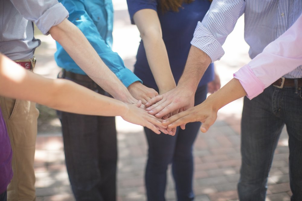 Stock photo of a team putting their hands in together (courtesy of Hubspot)