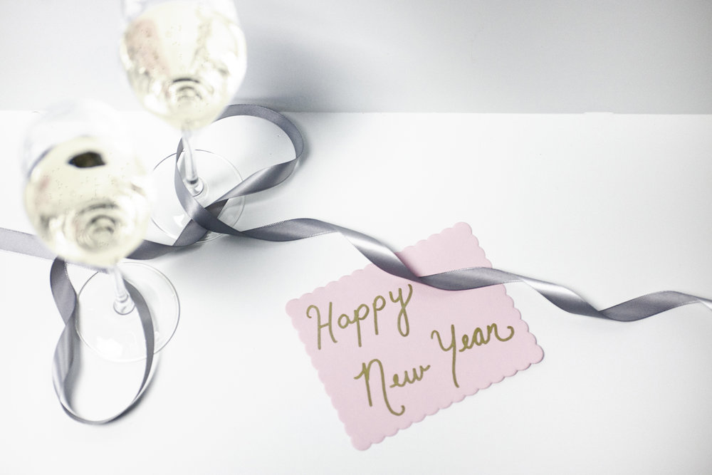 Stock image of a Happy New Years note with champagne glasses (courtesy of Hubspot)