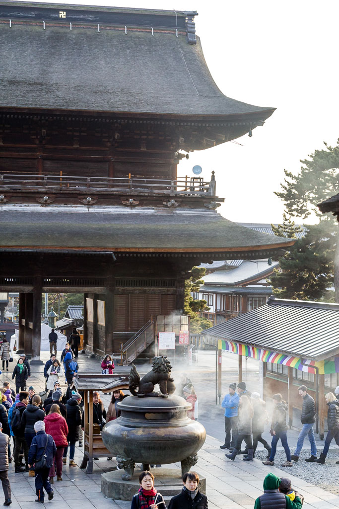 The smoke wafting from the lion incense burner in the Zenkoji temple courtyard.