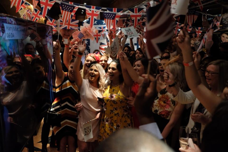 Harry's bar guests waving UK and US flags during ITV live feed.