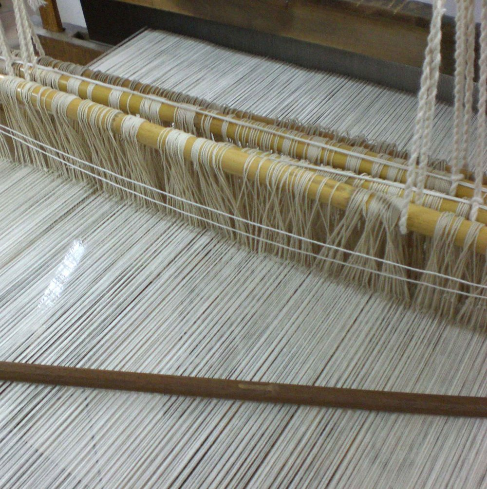 The weft treads are supported by local bamboo sticks.