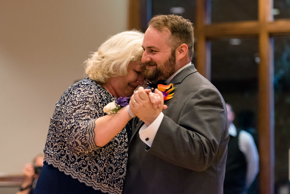 Groom and Mother Dance and Laugh during Happy Wedding Reception