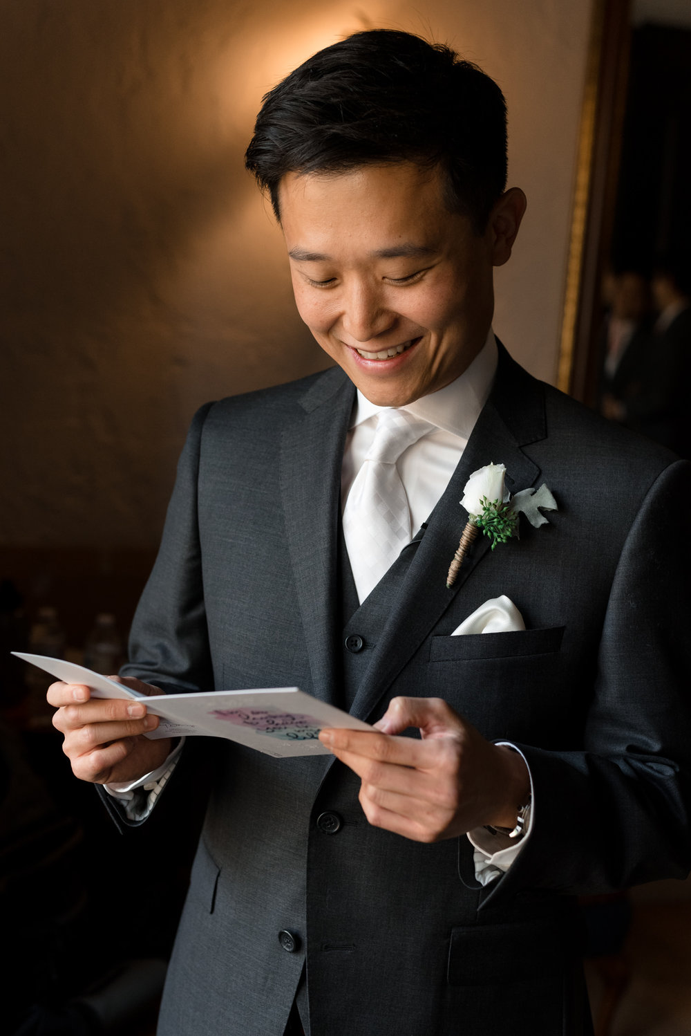Asian Groom Smiles and Reads Wedding Card from Bride