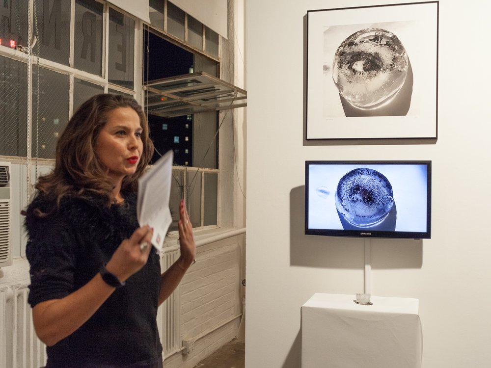Eszter giving an artist talk at the opening reception of  New Prints 2018/Winter.  Behind her, bottom to top: print on ice (on the pedestal), video of it melting, screenprint of a photograph of the ice block.