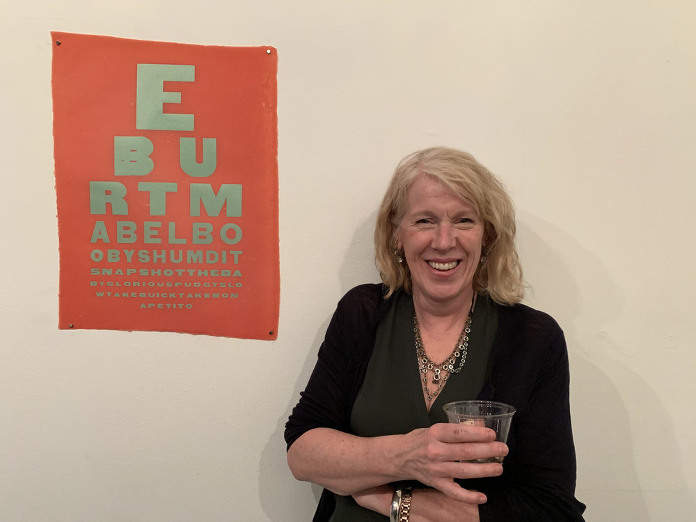 Ruth Lingen with her work, composed of nicknames that Richard Burton had for Elizabeth Taylor in eye chart format, made with letterpress from wood type on handmade paper.