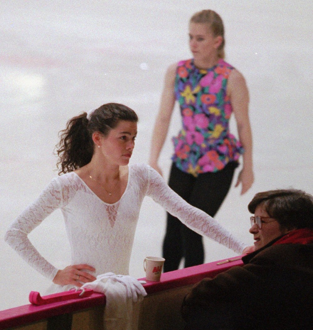 In the early 1990s, Nancy Kerrigan (front left) and Tonya Harding (back) were at the top of US figure skating.  While Kerrigan's competition outfits were often provided by sponsors, Harding often had to make her own outfits, harming her score in many competitions.