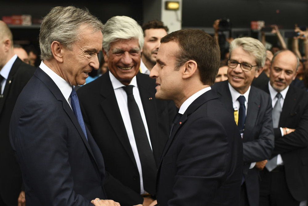 LVMH Group CEO Bernard Arnault (left) shakes the hand of French President Emmanuel Macron (right) at Vivatech // Image: Martin Bureau/Pool Photo via AP
