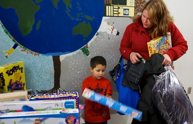 Kyree Crane, 4, shows his mom, Shawna Renollet, 26, a toy kit that included dinosaurs as they shop at HomePlate Youth Services' holiday store in Beaverton Wednesday night. He ended up getting the kit. Photo by Randy L. Rasmussen/The Oregonian